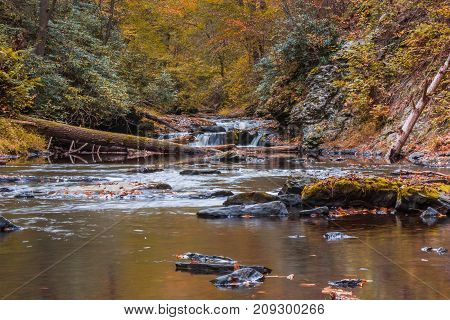 Water flows gently surrounded in peak fall foliage