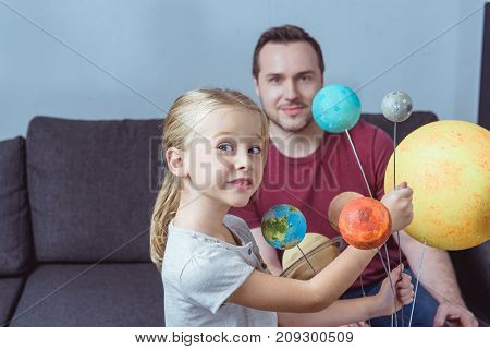 Father And Daughter Posing With Planets