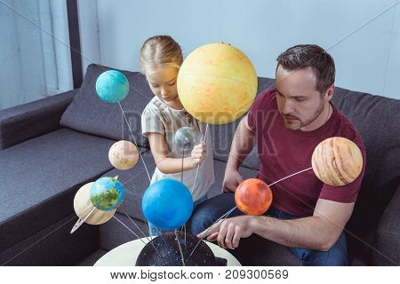 Father Showing Model Of Solar System