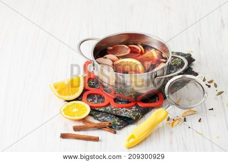 Cooked Mulled Wine In A Saucepan, Sieve, Oranges And Cinnamon