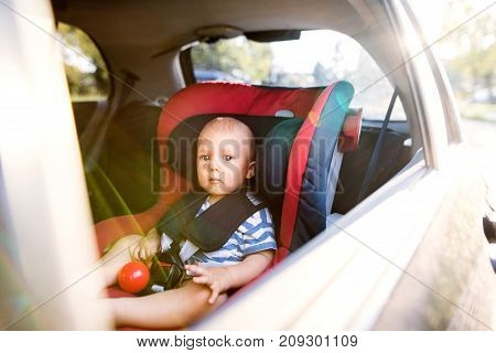 Cute little baby boy sitting in the car seat in the car, looking out.