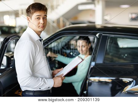 salesman presenting new car to clients auto dealership