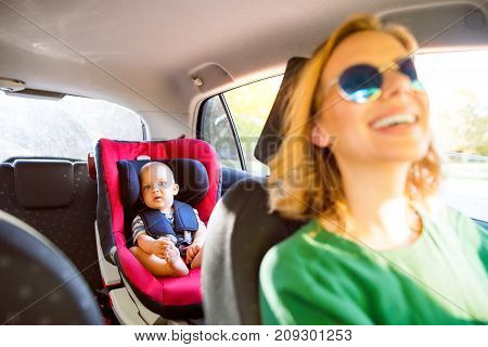 Young mother with her little son in the car. A woman driving and baby boy sitting in a car seat.