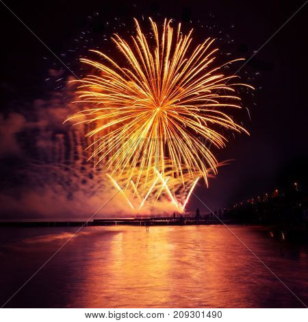 Festive fireworks of golden color on a black sky background