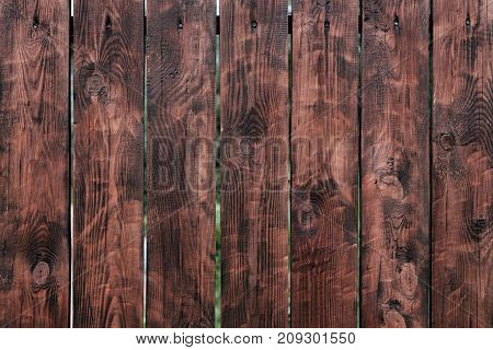 Brown, wooden board fence. Dark vintage wooden boards. burnt boards. Backgroundstextures fence painted. Front view. Attract beautiful vintage.