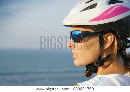 Profile view of woman on bike ride wearing protection helmet
