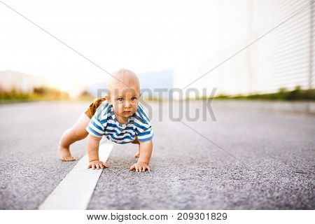 Cute little baby boy crawling outside on the road. Close up.