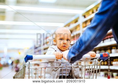 Unrecognizable young mother with her little baby boy at the supermarket, shopping.