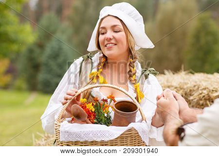 the peasant woman brought dinner to her man on the field. The husband holds the peasant woman by the hand