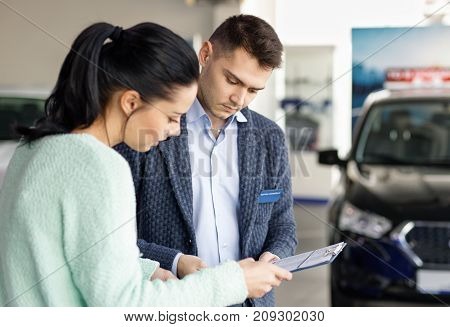 salesman presenting new car to clients in the background of dealership