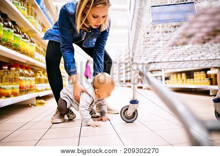 Beautiful young mother with her little baby boy at the supermarket, shopping.