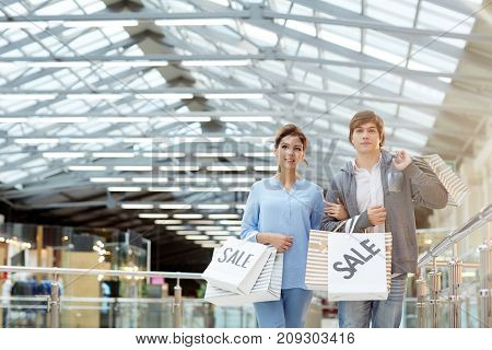 Amorous guy and girl with paperbags standing in large mall