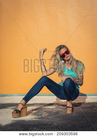 Beautiful blonde in sunglasses posing at the camera. Portrait on the background of bright orange wall. Modern hipster girl with tattoos. Sitting portrait.