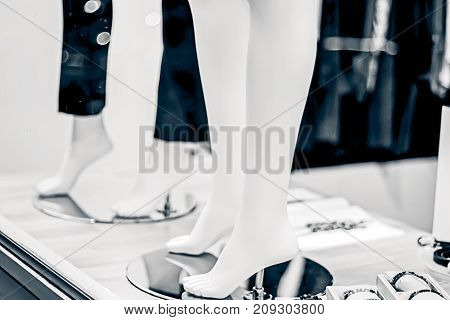 Legs of mannequins in trousers and without in the shop window