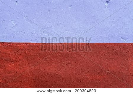 The homogeneous background of the wall is dyed with a brown and purple paint. In city in the fresh air. The background of the concrete fence.