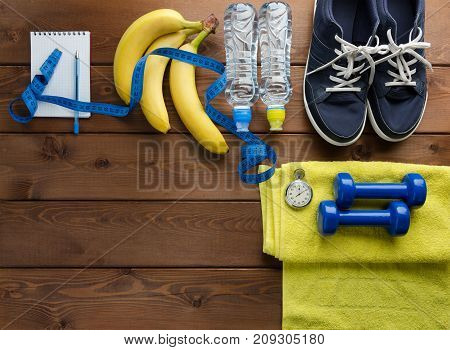 Fitness concept with sneakers dumbbells stopwatch measure tape towel bottle of water and bananas on wooden table background