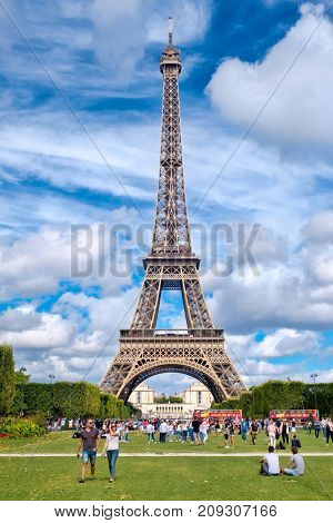 PARIS,FRANCE - JULY 30,2017 : The Eiffel Tower and tourists at the Champ de Mars on a summer day in Paris
