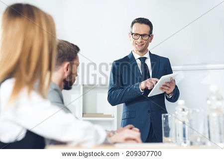 Businessman With Tablet Talking To Partners