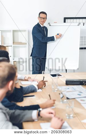 smiling mature businessman giving presentation at conference hall