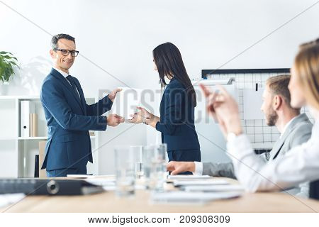 boss rewarding manageress while colleagues clapping to her