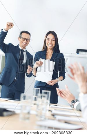 rewarded young manageress holding blank paper while colleagues clapping to her
