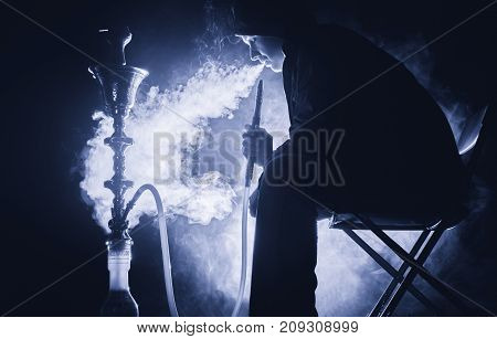 the person exhales thick smoke from a hookah