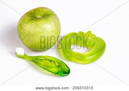 baby teeth care. green composition of apple toothbrush and teethers