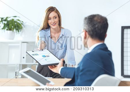 Businesswoman Passing Clipboard With Documents To Partner