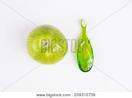 baby teeth care. green composition of toothbrush and teether on white background