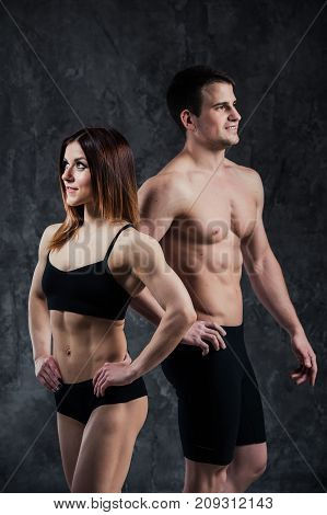 Fitness sporty healthy couple man and woman on a dark background.