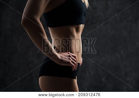 Side view of muscular fitness female model standing on black background. Young woman wearing sports bra looking down in thought