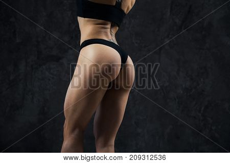 closeup of young female athlete back, trained buttocks, fit shape.