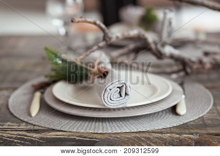 Vintage table setting, antique rustic napkin on dish and cutlery on the wooden background, close-up.
