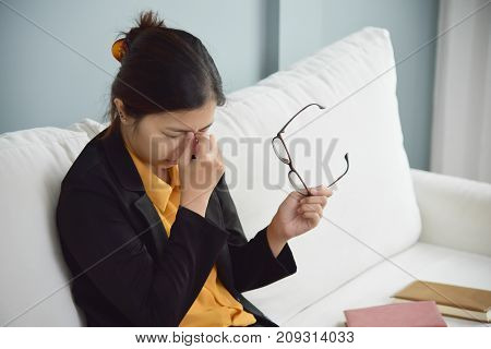 Tired Asian glasses woman rubbing eyes and sitting on white sofa. Copy space. Illness Exhausted from Overtime working concept. poster