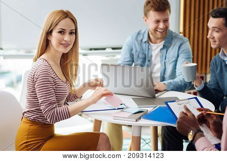 Pretty lady. Beautiful blonde keeping smile on her face and leaning arms on the table while looking straight at camera