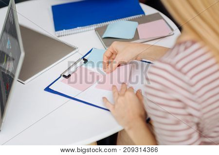 Put it here. Attentive blonde sitting at her workplace and putting sticker on her folder while preparing for presentation