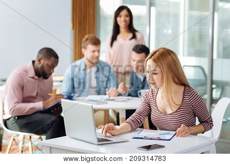 Press the button. Attentive blonde female looking at computer and leaning arms on table while sitting at her workplace