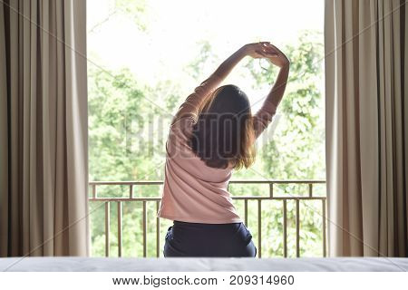 Rear view. Happy Relaxed Asian woman waking up and stretching her arms on green natural background at her bedroom in the morning. Resting on Holiday.