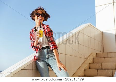 Young teenage girl in sunglasses drinking orange juice with a straw while standing and laughing on steps outdoors