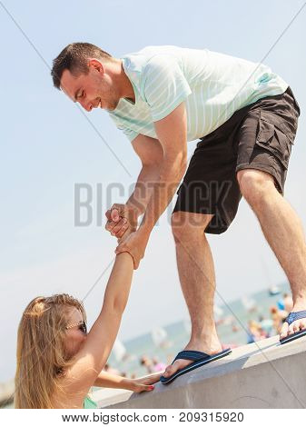 Man Helping Girlfriend To Get On Fenece