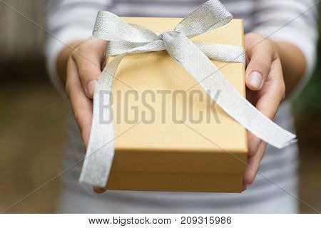Golden gift box in hand for giving in holidays