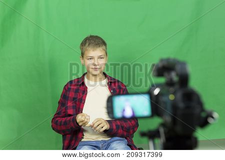 Young Boy Blogger Records Video On A Green Background