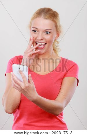 Fun with technology modern devices concept. Attractive smiling happy excited blonde woman checking social media on smartphone.