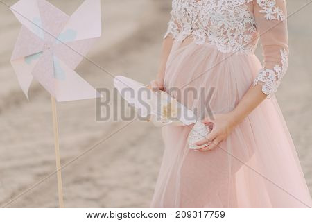 the pregnant girl on the river bank on a sunset