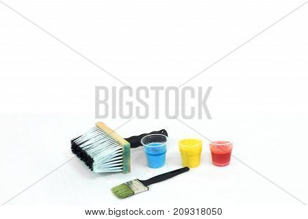 Big and small paintbrushes and blue, yellow and red stains - bottom mock up