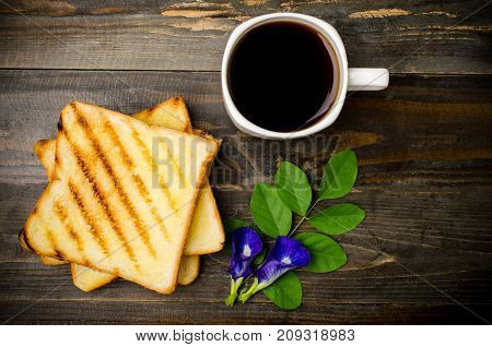 Toast and cup of coffee on wooden table, top view
