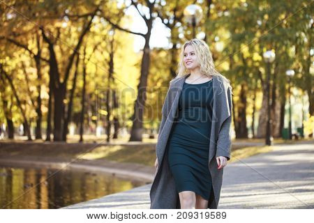 Portrait of a young beautiful blonde woman in gray coat on a background of autumn park