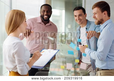 Friendly group. Positive delighted men standing together near glass board and keeping smile on faces while looking at their partner
