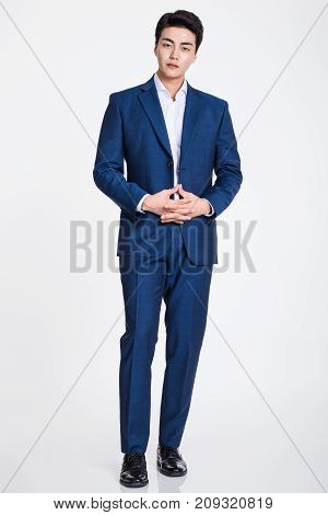 Studio portrait of a confident businessman posing against a gray background