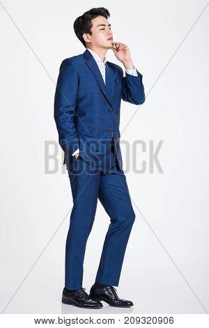Studio portrait of a confident businessman posing against a gray background